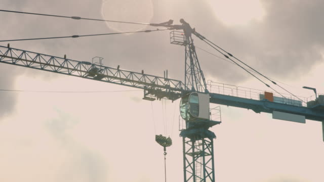 construction crane on a cloudy sky - crane stock videos & royalty-free footage