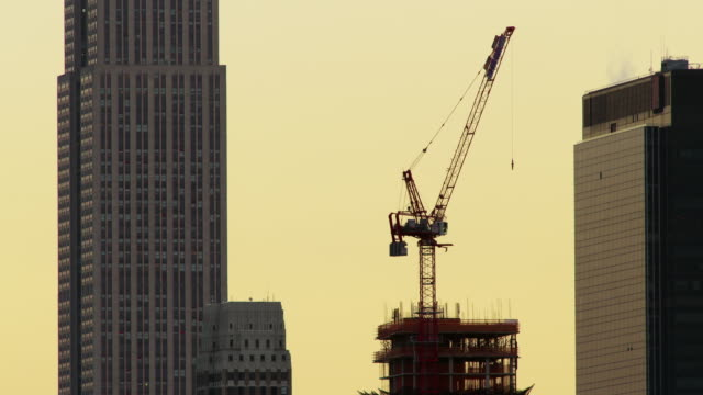 Construction crane stands atop skyscraper being built against a yellow sky. Steam rises out from nearby building top.