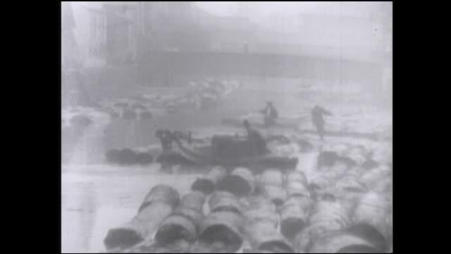 vidéos et rushes de a construction crane towers over a japanese lumberyard; logs float in the river. - chantier de scierie