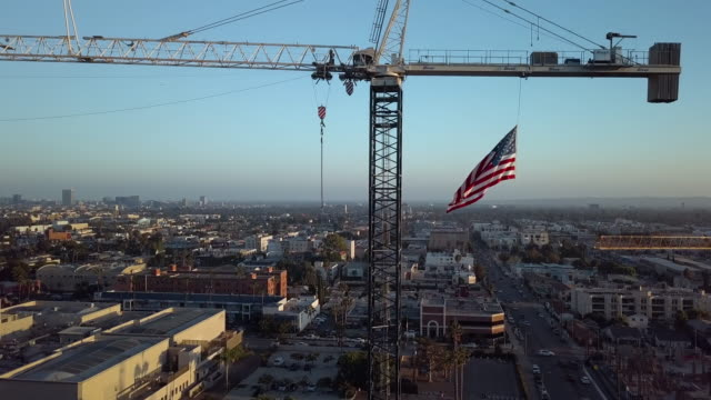 construction crane with american flag- aerial drone shot - american flag stock videos & royalty-free footage
