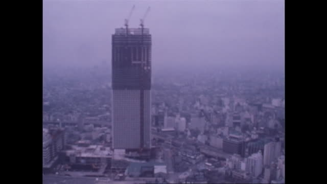 construction cranes are atop the sunshine 60 building under construction in downtown tokyo. - showa period stock videos & royalty-free footage