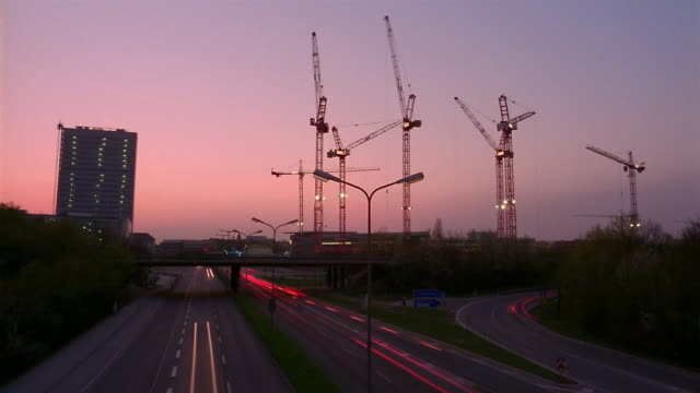 Construction cranes move as a colorful sky darkens.