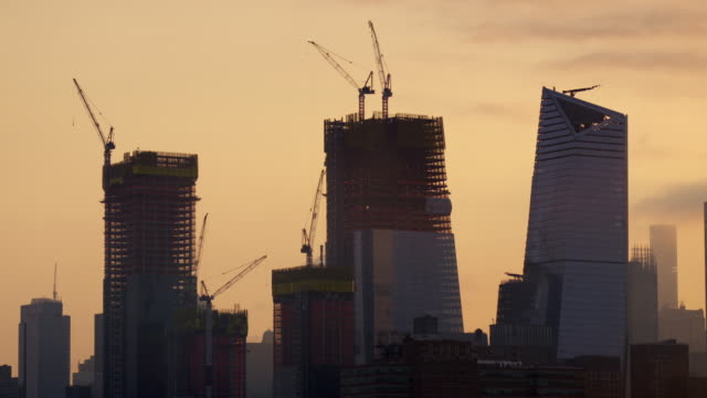 construction cranes move material up and down skyscrapers currently being built. - construction material stock videos and b-roll footage