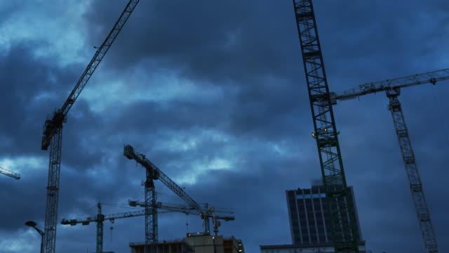 vídeos de stock e filmes b-roll de construction cranes on a dark, cloudy sky. construction site after sunset - objeto manufaturado