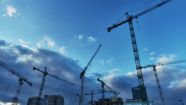 construction cranes on a dark, cloudy sky - large stock videos & royalty-free footage