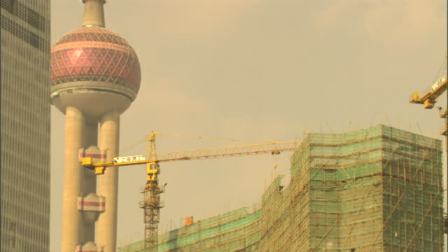 construction cranes surround skyscrapers near the oriental pearl tower in shanghai, china. - oriental pearl tower shanghai stock videos & royalty-free footage