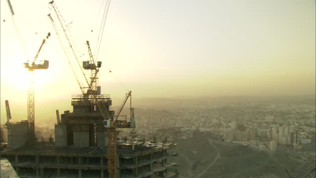vídeos y material grabado en eventos de stock de construction cranes top the roof of a tall skyscraper in saudi arabia. - arabia