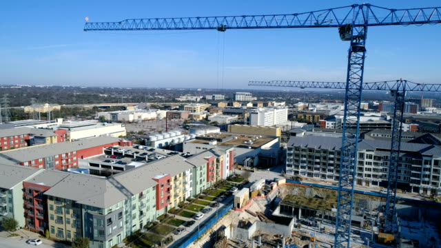 construction cranes with buildings blue sky and blue cranes building a new development side pan across constrcution site - scaffolding stock videos & royalty-free footage