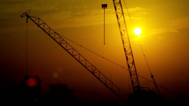 vídeos y material grabado en eventos de stock de construction cranes working sunrise silhouette above skyline dubai - golfo pérsico