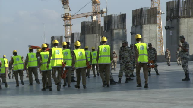 a construction crew carries equipment past soldiers at a military base. - saudi arabia stock videos & royalty-free footage