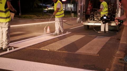 stockvideo's en b-roll-footage met bouw bemanning spray schilderij crosswalk strepen 's nachts - work tool