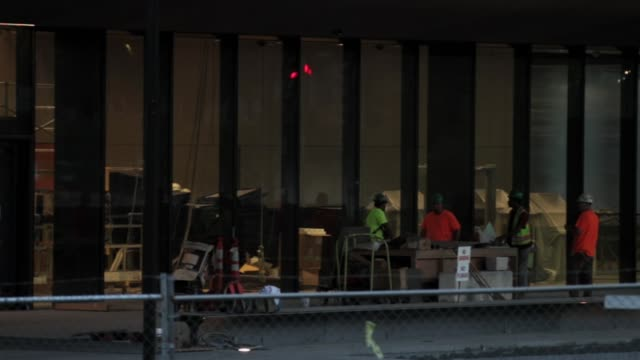 vídeos de stock, filmes e b-roll de a construction crew works in front of the entrance cover of the soontobeopened smithsonian national museum of african american history and culture... - smithsonian institution