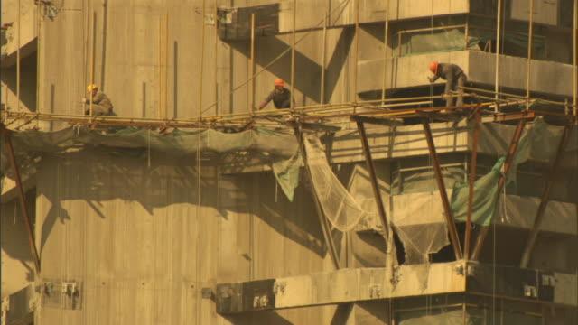 a construction crew works on scaffolding. - 足場点の映像素材/bロール