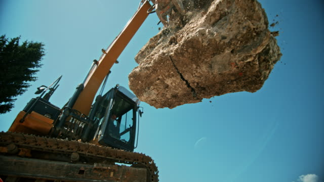 vídeos de stock e filmes b-roll de slo mo construction debris being released from the excavator and falling on a pile in sunshine - maquinaria de construção