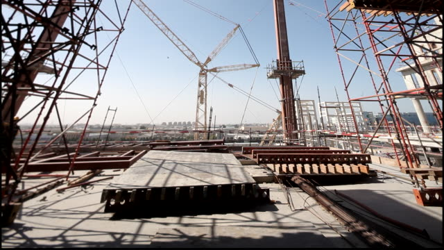 vídeos y material grabado en eventos de stock de construction, dubai. shot taken from the roof of a construction site in dubai, showing scaffolding, girders, cranes, wall sections, dubai skyline in... - torre estructura de edificio