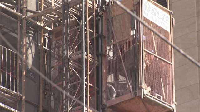 a construction elevator moves past scaffolding on a high rise in beijing. - 足場点の映像素材/bロール