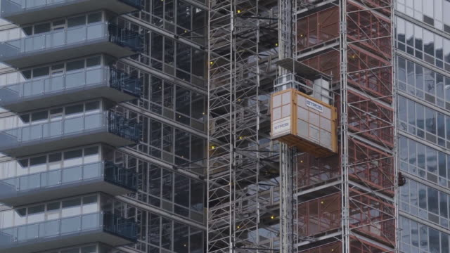 Construction elevators travel up and down a building in progress