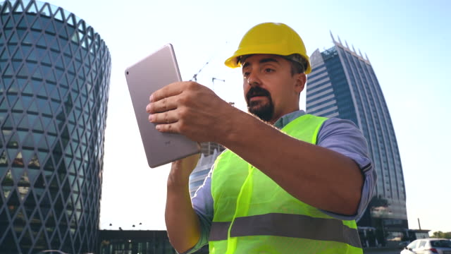 construction engineer, architect or construction worker using digital tablet for video call , modern skyscrapers in background, slow motion - hardhat stock videos & royalty-free footage