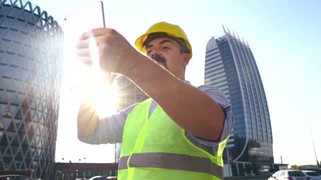 vídeos de stock, filmes e b-roll de engenheiro de construção, arquiteto ou pedreiro usando tablet digital para chamada de vídeo, arranha-céus modernos em segundo plano, câmera lenta - capacete equipamento
