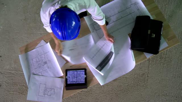 hd crane: construction engineer examining the blueprints - intelligence stock videos & royalty-free footage
