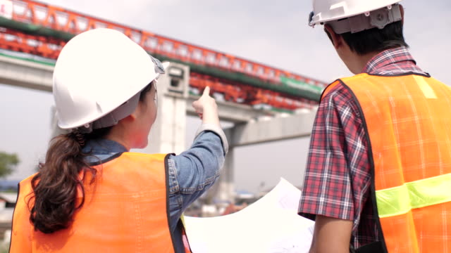 工事現場での建設作業員に指示を与える建設エンジニア - 建設現場点の映像素材/bロール