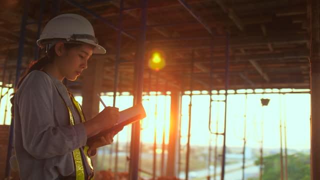 vidéos et rushes de l'ingénieur en construction vérifie avec la tablette numérique et le plan directeur - symbole