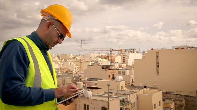 A construction engineer uses a tablet to calculate costs