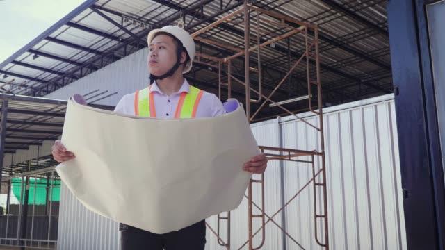 建設エンジニア建物の設計図では建設現場での作業 - ヘルメット点の映像素材/bロール