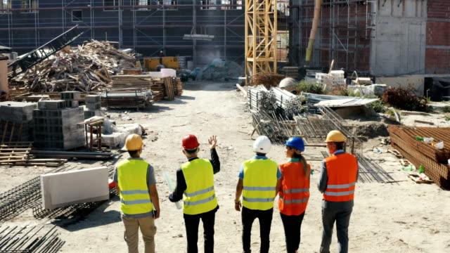 vidéos et rushes de ingénieurs en construction ayant une réunion sur le chantier. - classe ouvrière