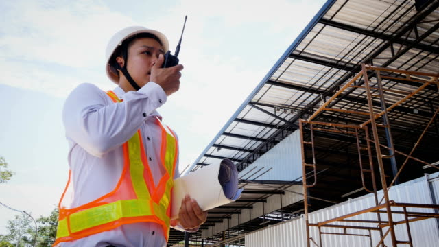 Construction engineers using walkies-talkie at construction site