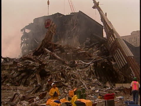 construction equipment clears the mountains of smoking rubble at ground zero with several still-standing skyscrapers in the distance. - land stock videos & royalty-free footage