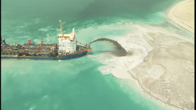 construction equipment distributes soil and sand from the seabed to form a man-made island in the persian gulf. - cargo ship stock videos & royalty-free footage