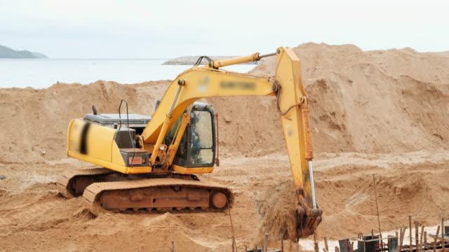 vidéos et rushes de construction : machine d'excavatrice avec le sol de chargement de pelle au camion de benne sur le chantier de construction. excavatrice industrielle de chargeuse de camion déplaçant la terre et déchargeant dans un camion de dumper - pelleteuse