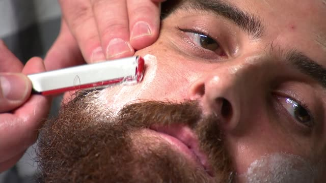 construction firm bans beards over health and safety r21091516 / 2192015 london int bearded man being shaved with cut throat razor man having beard... - health and safety点の映像素材/bロール