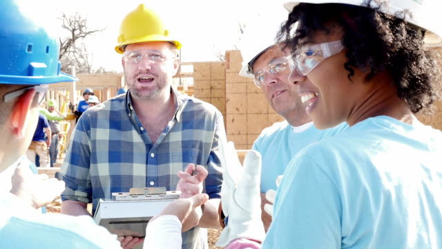 Construction foreman explains project to volunteers building home for charity