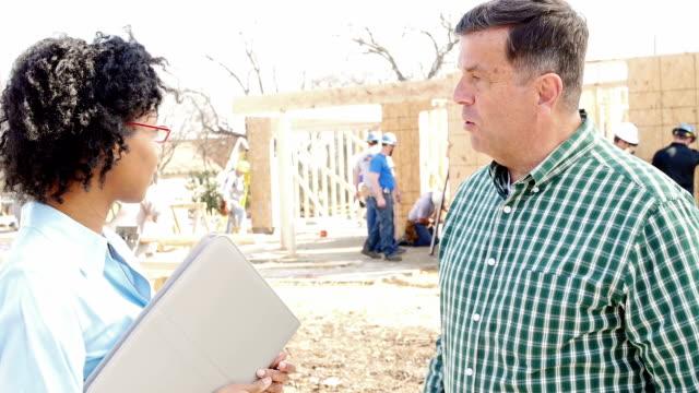 Bouw foreman begroet executive bij bouwplaats