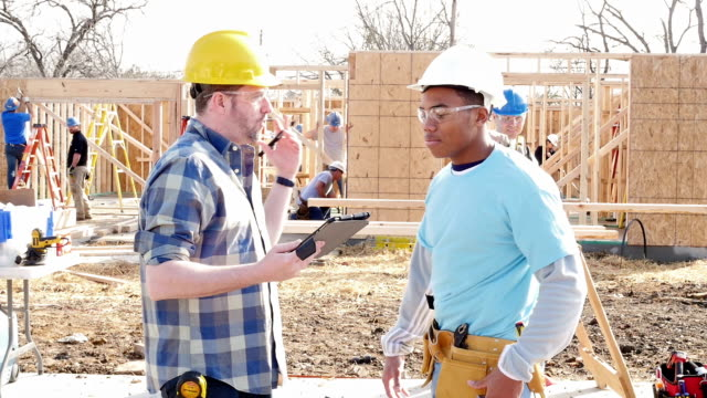 construction foreman with digital tablet instructing volunteer while building home - tool belt stock videos and b-roll footage