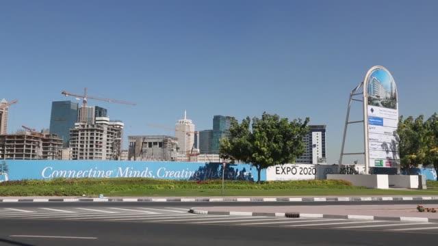 stockvideo's en b-roll-footage met construction hoardings advertising expo 2020 stand in front of skyscraper properties under construction in dubai, united arab emirates , on sunday,... - kerktoren