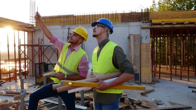 vidéos et rushes de industrie de la construction - architectes et ingénieurs travaillent ensemble - classe ouvrière