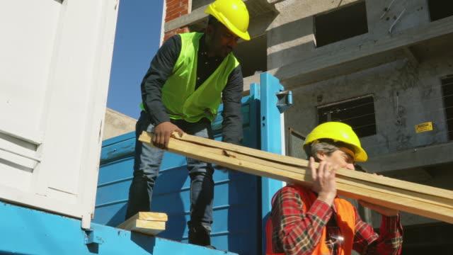 konstruktionsarbete lossnings plankor från lastbil - bära bildbanksvideor och videomaterial från bakom kulisserna
