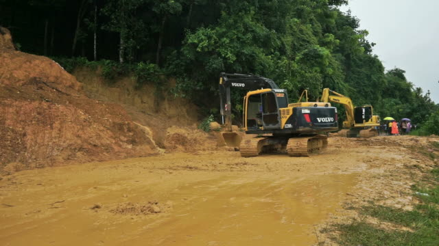 vídeos de stock, filmes e b-roll de construction machinery diggers clearing landslide from the road - erodido