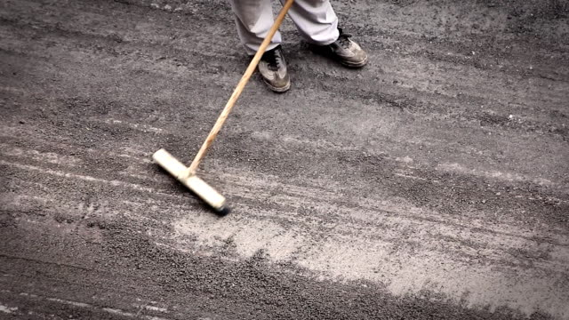 Construction man sweeping the road