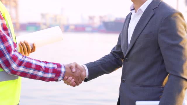 construction manager and engineer shaking hands on port - berufliche partnerschaft stock-videos und b-roll-filmmaterial
