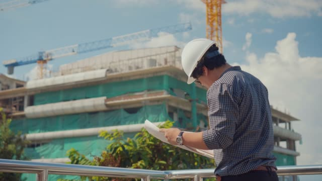 construction manager reviewing blueprints at construction site,dolly shot - architetto video stock e b–roll