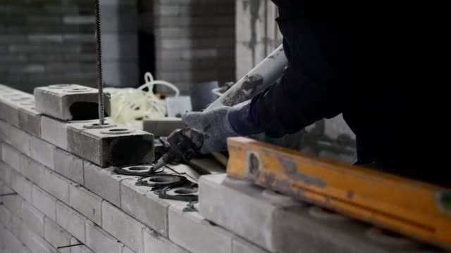 construction of a brick wall. - caulk gun stock videos and b-roll footage