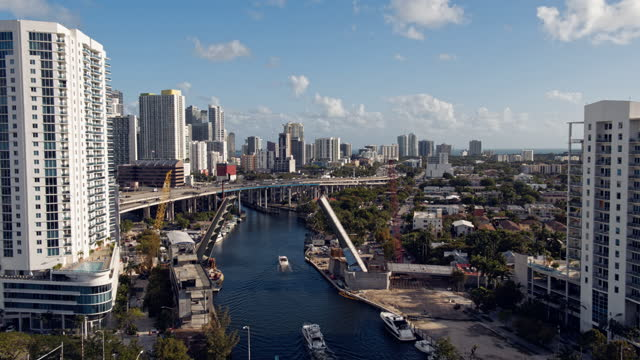 construction of a new drawbridge on miami river between downtown miami and the residential east little havana neighborhood. aerial footage with cinematic forward and descending camera motion, passing between the opened sections of the bridge - bascule bridge stock videos & royalty-free footage