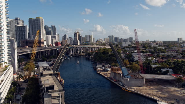 construction of a new drawbridge on miami river near downtown miami and interstate-95 highway, florida. aerial footage with the forward camera motion, flying between the opened sections of the bridge. - bascule bridge stock videos & royalty-free footage