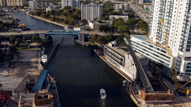 construction of a new drawbridge on miami river, with a view toward residential spring garden and overtown districts of miami, florida. a boat is passing on the river. aerial footage with the cinematic forward and tilting-down camera motion. - bascule bridge stock videos & royalty-free footage