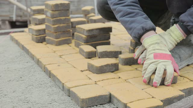vídeos de stock e filmes b-roll de construction of a sidewalk from yellow paving stones. - membro humano