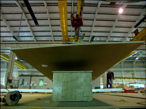 construction of kit homes as they move along assembly line on factory floor - erezione video stock e b–roll
